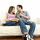 Man and woman enjoying beer with pizza