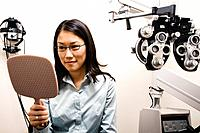 Asian woman trying on eyeglasses