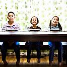 Asian siblings sitting at dinner table
