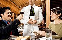 Asian man testing wine at restaurant
