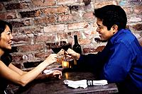 Asian couple toasting with wine