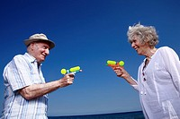 Senior couple on beach with water guns (thumbnail)