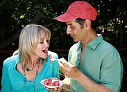 Mature adult couple eating watermelon