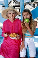 Grandmother and granddaughter eating at beach