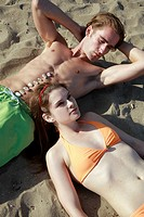 Young adult couple lying on beach
