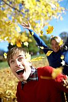 Playful woman throwing leaves at man (thumbnail)