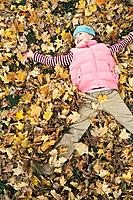 Girl playing in leaves