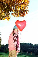 Girl holding a heart shaped balloon