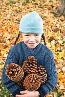 Girl with an armful of pine cones