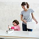 Mother watching daughter use glue brush