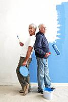 Two men standing in half painted room
