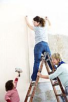 Family putting up wallpaper together