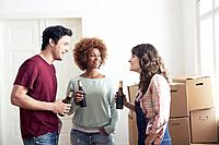Roommates enjoying beer in new apartment