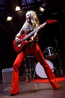 rock band woman performing on stage, playing electric guitar