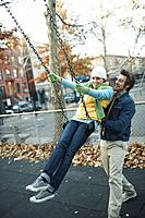 Man pushing woman on a swing