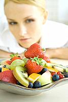 Woman looking at plate of fruit salad
