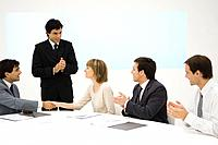 Business associates at conference table, two shaking hands, the others clapping