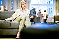 Woman Testing Sofa in Furniture Store