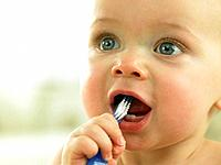 Baby's face close up with toothbrush in mouth