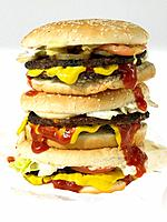 Three beef burgers with toppings in take out packaging (thumbnail)