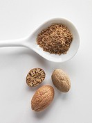 Nutmegs, whole, half and grated on a porcelain spoon