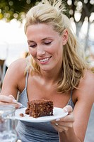 Young woman in summer clothes eating a piece of cake