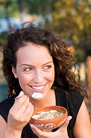 Woman eating yoghurt with honey and grated nuts