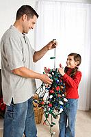 Father and daughter with tangled Christmas lights
