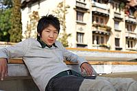 Teenage boy sitting on bench