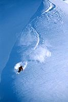Aerial of skier slaloming down backcountry peak Chugach Mountains near Valdez SC Alaska Winter