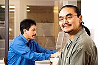 Alaskan native men working at computer terminal in office environment Alaska Yupik & Inupiat