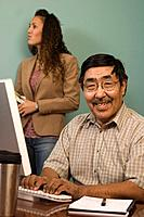 Alaskan native man & women working at computer in office setting Anchorage AK Yupik & Inupiat descent