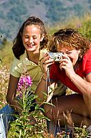 Mother & daughters taking picture of wildflower along Coastal Trail on Turnagain Arm, Southcentral Alaska.