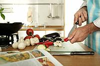 Young man cutting vegetables in kitchen, close_up