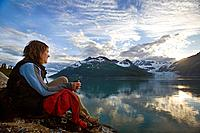 Woman overlooking Surprise Glacier at sunset Harriman Fjord PWS Southcentral Alaska summer