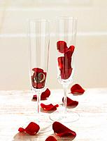 Champagne glasses filled with rose petals and wedding rings
