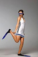 Young woman wearing goggles and flippers, studio shot
