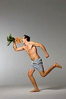 Mid adult man holding carrots while running