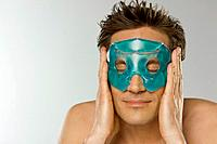 Mid adult man holding eye mask