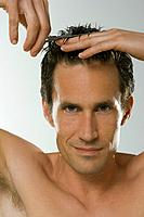 Close_up of mid adult man clipping hair