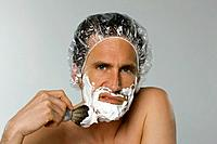 Mid adult man brushing on shaving cream