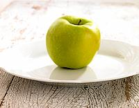 Close_up of a granny smith apple in a plate