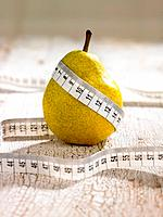 Close_up of a tape measure wrapped around a pear