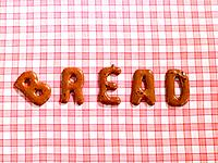 Word BREAD on a tablecloth made from alphabet biscuits
