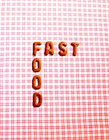 Word FAST FOOD on a tablecloth made from alphabet biscuits