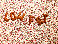 Word LOW FAT on a tablecloth made from alphabet biscuits