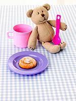 Close_up of a teddy bear with a cup and a plate