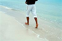 Man walking barefoot on beach