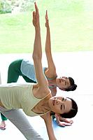 Two Young Women Practicing Yoga, Bending Body, Right Arms Up, Front View