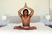 Man sitting in cross_legged yoga position in bed